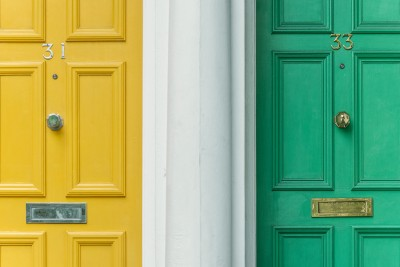 a yellow door and a green door with a white column in between